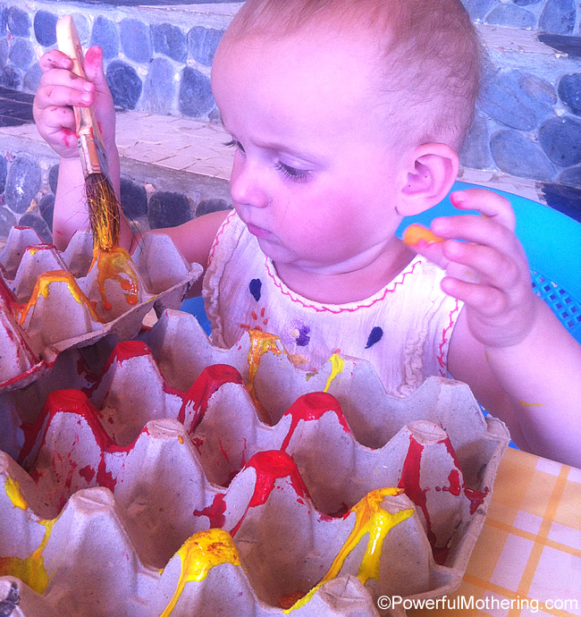 1 year old having fun painting the egg cartons