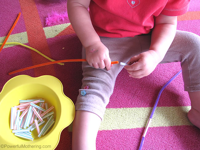 threading straws onto the pipe cleaners