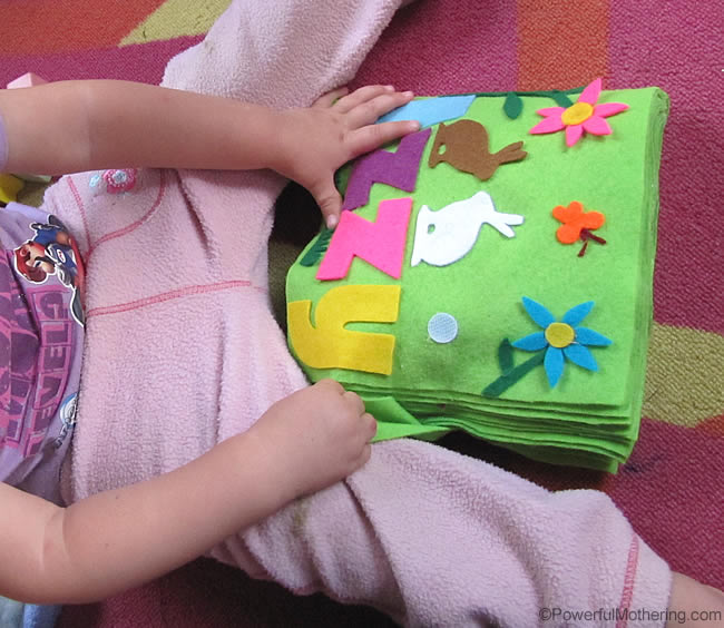 a little girl very happy with her felt book
