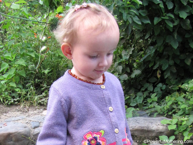 little girl wearing amber teething necklace