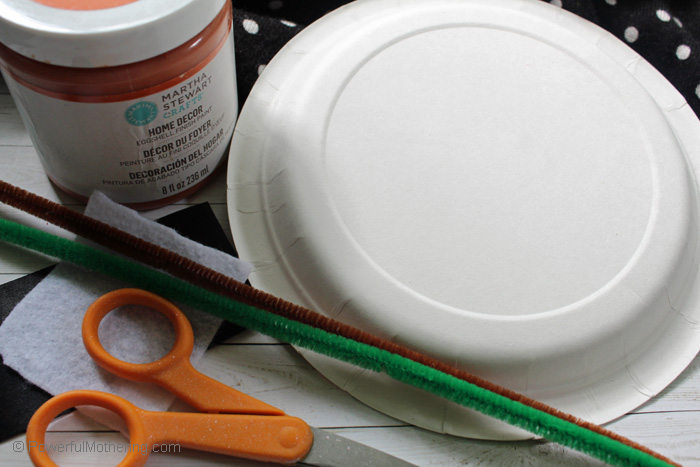Supplies needed to make this adorable paper plate pumpkin craft with your kids.